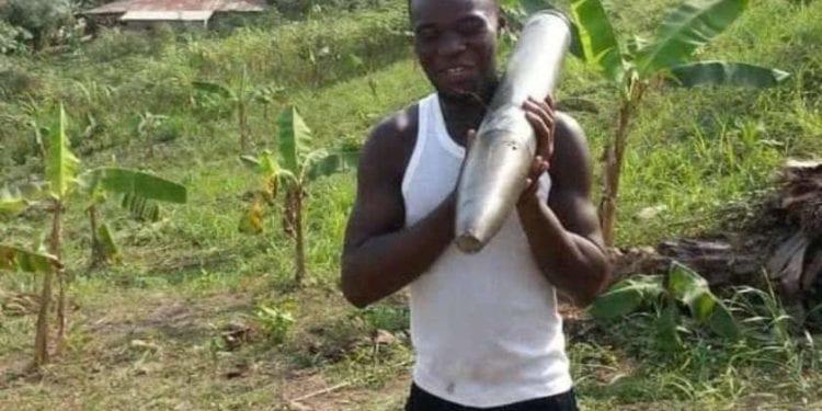 Un ciudadano de Bata se posa con un proyectil después de haberlo encontrado