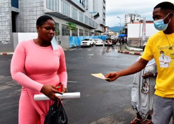 Un joven voluntario entregando afiche a una señora con la mascarrillas colgada en la oreja